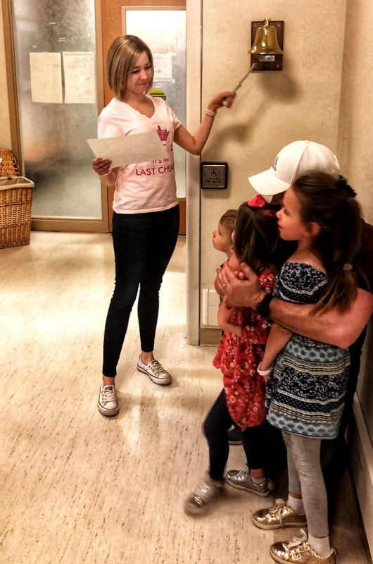 Marisa ringing the bell with her daughters
